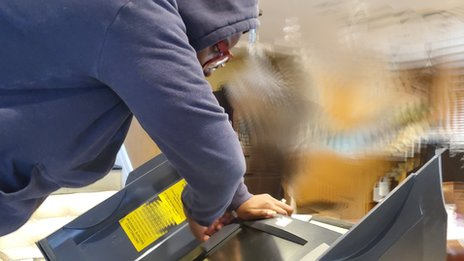 Beatrice Atobatele taking apart her voting machine to test it
